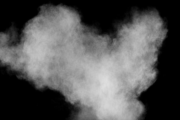 Bizarre forms of white powder explosion cloud against black background.white dust particles splash.