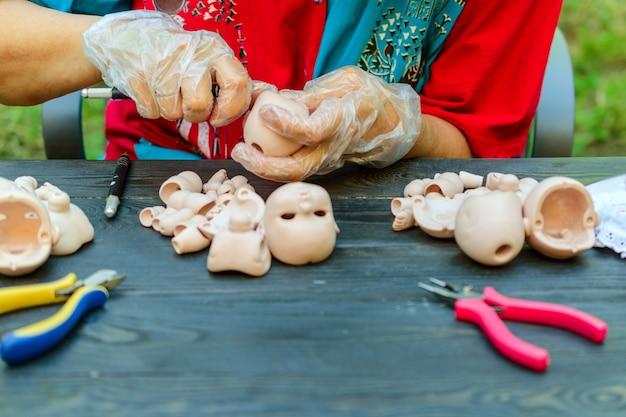 女性の手は職場でbjdの人形を作る。ワークピースを処理する。
