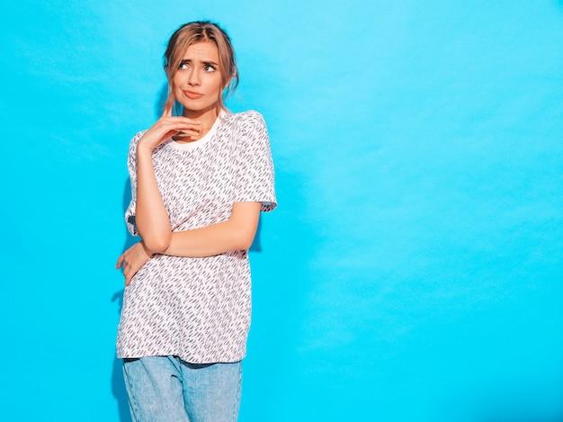 Молодая красивая битник вдумчивый девушка в модных летних джинсовой одежде. сексуальная беззаботная женщина позирует возле bkue стены в студии. смотреть в сторону. концепция выбора
