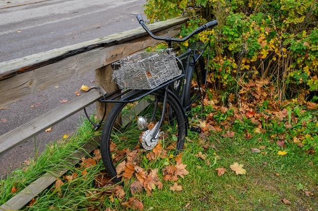 Черный заброшенный велосипед с корзиной.