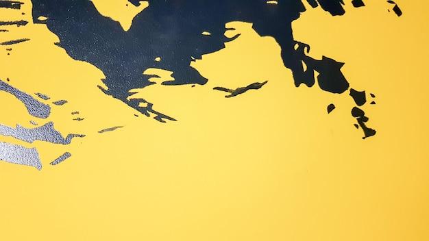 黒の抽象的なペンキが明るい黄色の背景に滴り落ちる。黄色の背景に黒いペンキがはねかけます。アートのアイデアの概念。背景にブラシテクスチャを黄色と黒でペイントします。