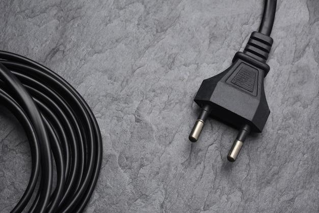 Черная вилка переменного тока типа c на текстуре или фоне черного сланца