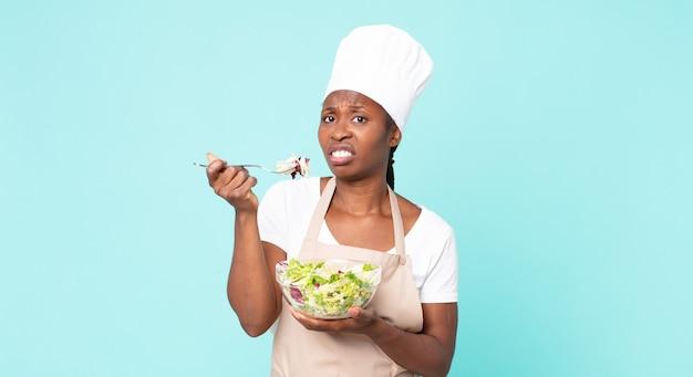 サラダを持っている黒人アフリカ系アメリカ人の大人のシェフの女性