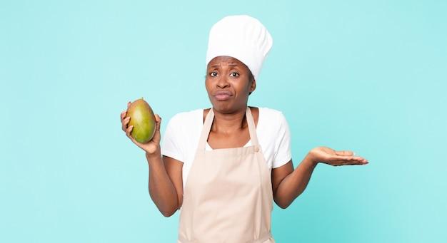 黒人のアフリカ系アメリカ人の大人のシェフの女性がマンゴーを持っています