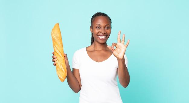 バゲットを保持している黒人アフリカ系アメリカ人の成人女性