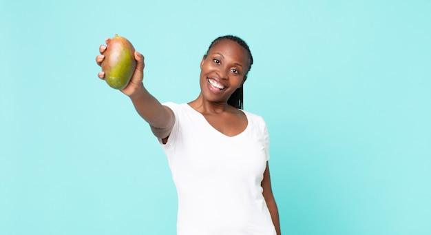 マンゴーの果実を保持している黒人アフリカ系アメリカ人の大人の女性