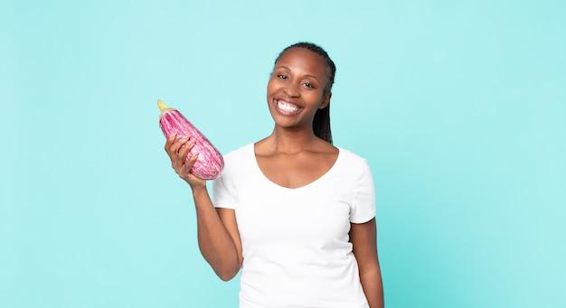 Черная афро-американская взрослая женщина, держащая баклажан