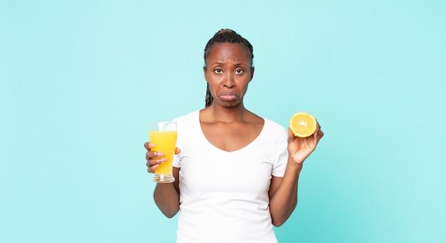 黒人のアフリカ系アメリカ人の成人女性。オレンジジュースのコンセプト