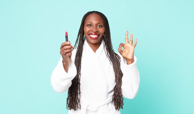 バスローブを着て、口紅を持っている黒人のアフリカ系アメリカ人の大人の女性