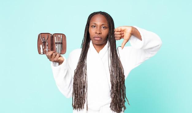 バスローブを着て、nainsツールでメイクアップバッグを保持している黒人のアフリカ系アメリカ人の大人の女性