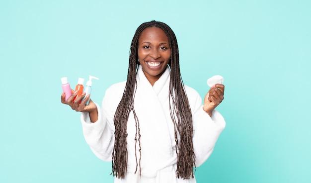 Чернокожая афро-американская взрослая женщина в халате и держит косметические продукты
