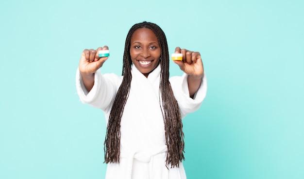 Чернокожая афро-американская взрослая женщина в халате и косметических продуктах