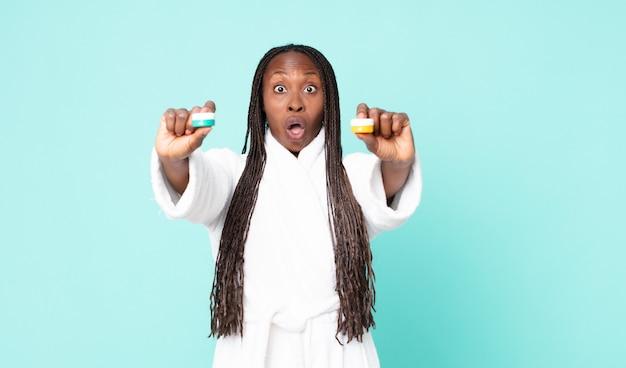 Афроамериканская взрослая женщина в халате с косметическими продуктами