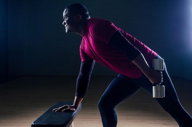 Чернокожий афро-американский спортивный мужчина работает на беговых дорожках, делая упражнения на группы мышц, отжимаясь от скамейки в спортзале на черном фоне