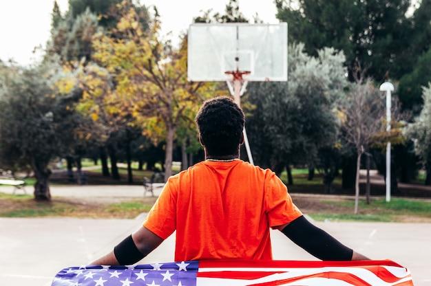 도시 농구 코트에 미국 국기를 들고 흑인 아프리카 계 미국인 소년. 오렌지색 티셔츠를 입고.