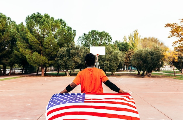 Black african-american boy carrying the u.s. flag on an urban basketball court. dressed with an orange t-shirt.