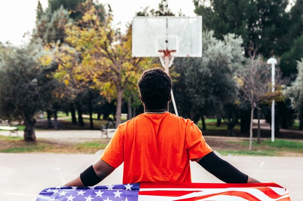 Black african-american boy carrying the u.s. flag on an urban basketball court. dressed with an orange t-shirt. Premium Photo