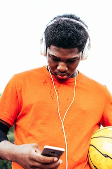 Black african-american boy listening to music with headphones and his mobile phone after playing basketball on an urban court. dressed with an orange t-shirt.