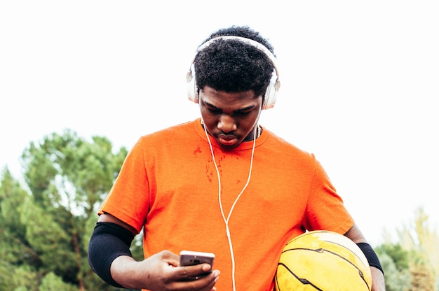 Black african-american boy listening to music with headphones and his mobile phone after playing basketball on an urban court.