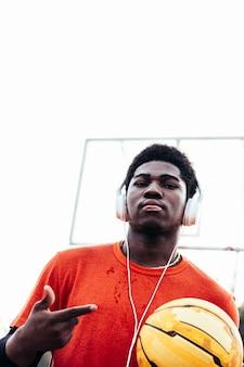 도시 법원에서 농구 후 헤드폰 및 그의 휴대 전화로 음악을 듣고 흑인 아프리카 계 미국인 소년. 오렌지색 티셔츠를 입고.