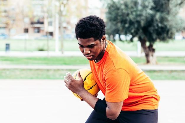 Черный афро-американский мальчик играет в баскетбол с желтым мячом на городской площадке. одета в оранжевую футболку.