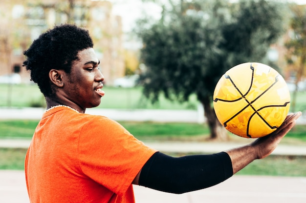 Черный афро-американский мальчик играет в баскетбол с желтым мячом на городской площадке.
