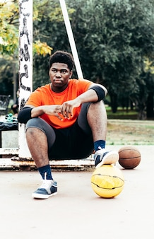 Черный афро-американский мальчик отдыхает после игры в баскетбол. одета в оранжевую футболку.