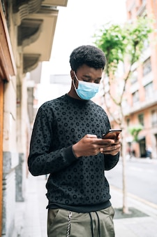 Black african american boy walking down the street with a blue face mask looking at his cell phone protecting himself from the covid-19 coronavirus pandemic