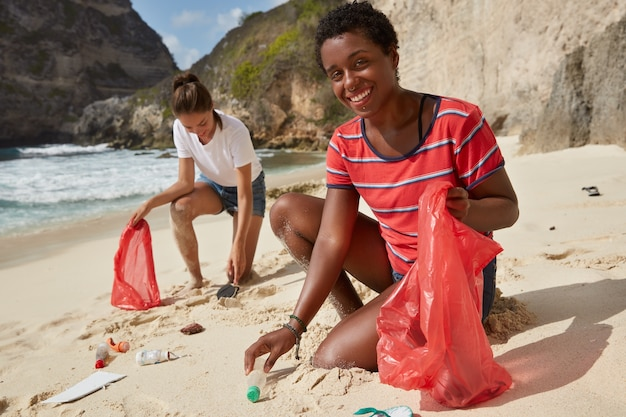 Una donna afroamericana di colore e il suo compagno raccolgono bottiglie di plastica riciclabili e altri rifiuti