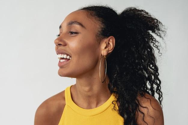 흰색 외진 배경에 세련된 힙스터 복장을 한 흑인 흑인 여성, 여름 패션 트렌드, 행복한 미소 곱슬머리 액세서리 귀걸이