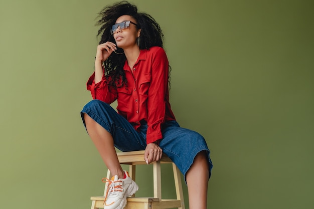 Black african american woman in stylish outfit jeans and red blouse isolated on green