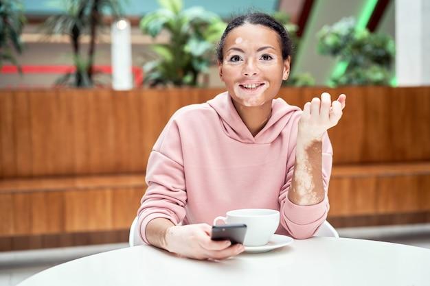 白斑色素沈着の皮膚の問題を持つ黒人アフリカ系アメリカ人女性スマートフォンを使用して屋内服を着たピンクのパーカー座っているテーブル