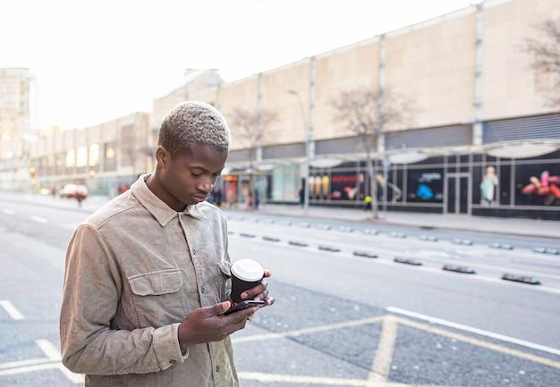 通りでスマートフォンとコーヒーを持っている黒人のアフリカの少年学生