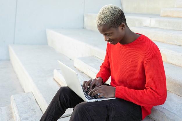 ラップトップを持つ黒人アフリカの少年幸せで笑顔白い背景の上の階段に座って