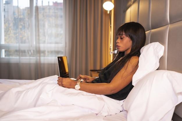 コンピューターで作業しているホテルのベッドで黒人アフリカの民族の女の子。仕事の新しい正常性