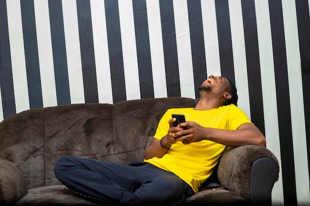 모바일 장치를 사용하여 소셜 네트워크에서 친구와 채팅하는 흑인 아프리카 남성 힙스터