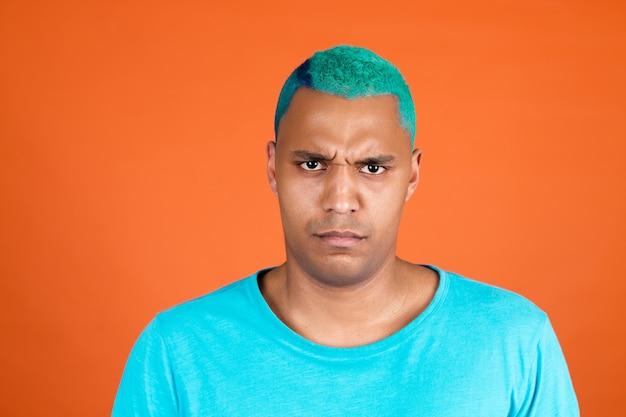 L'uomo africano nero in casual sui capelli blu della parete arancione aggrotta le sopracciglia non è d'accordo deluso serio
