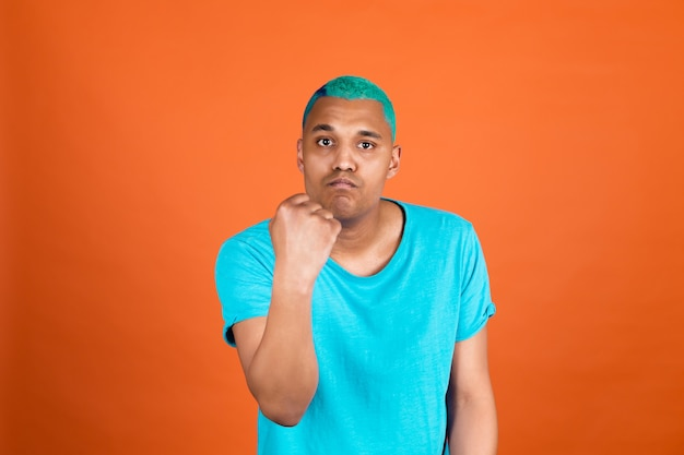 Black african man in casual on orange wall blue hair shouting angry raising fist unhappy and aggressive