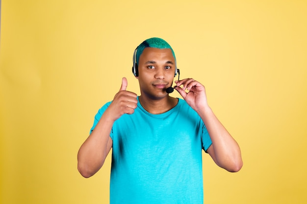Black african man in casual on yellow wall blue hair call centre worker happy customer support operator with headphones show thumb up