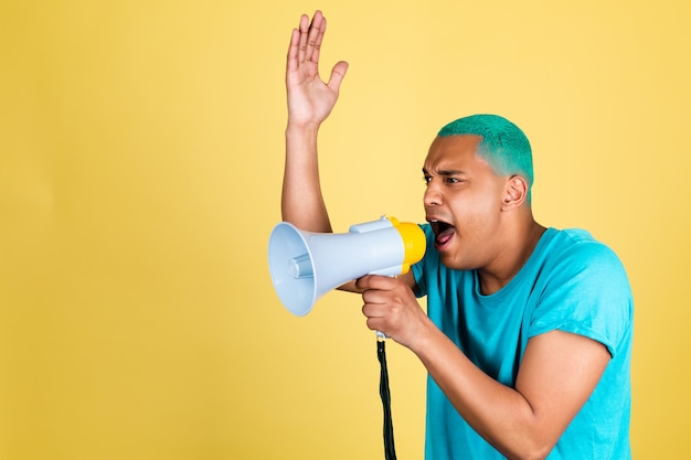 Black african man in casual on yellow wall blue hair screaming shouting in megaphone to left