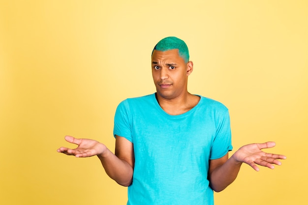 Black african man in casual on yellow wall look to camera shrugging shoulders clueless and confused