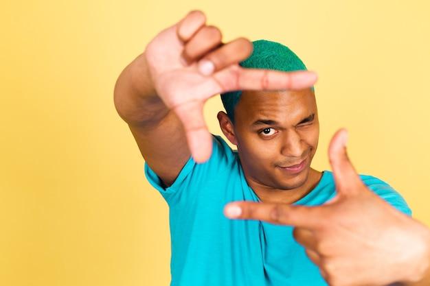L'uomo africano nero in casual sulla parete gialla che fa la cornice della foto con le mani con un occhio chiuso scatta una foto