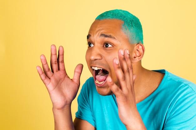 Uomo africano nero in casual sulla parete gialla che grida ad alta voce con la bocca spalancata, urlando