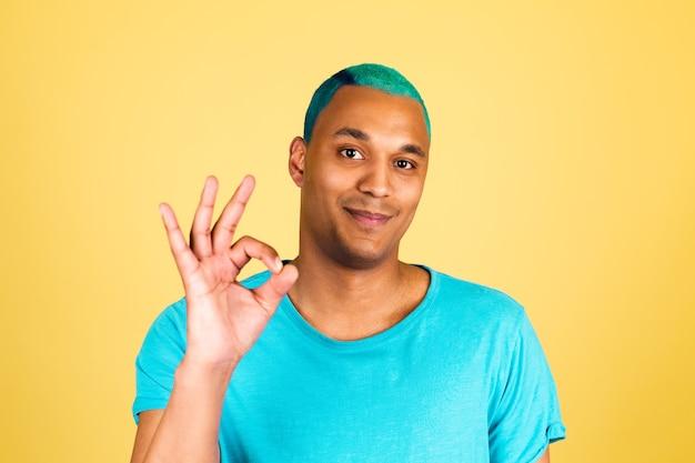 黄色の壁にカジュアルな黒人アフリカ人男性が笑顔でカメラに幸せな表情を見せてokジェスチャー