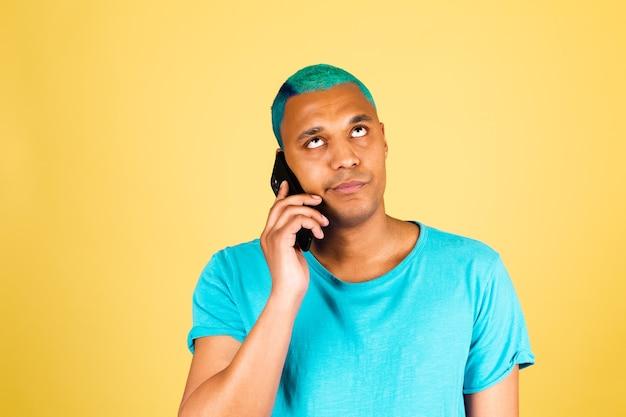 휴대 전화와 노란색 벽에 캐주얼에 흑인 아프리카 남자는 지루한 피곤한 얼굴로 목소리를 들어