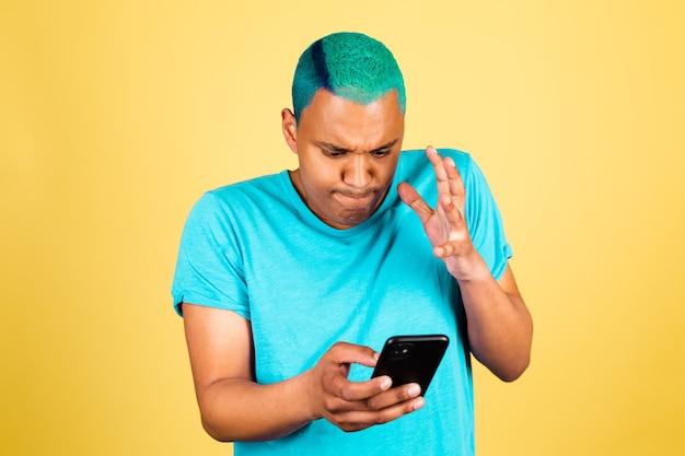 Черный африканский мужчина в повседневной одежде на желтой стене с мобильным телефоном выглядит сердитым и возмущенным