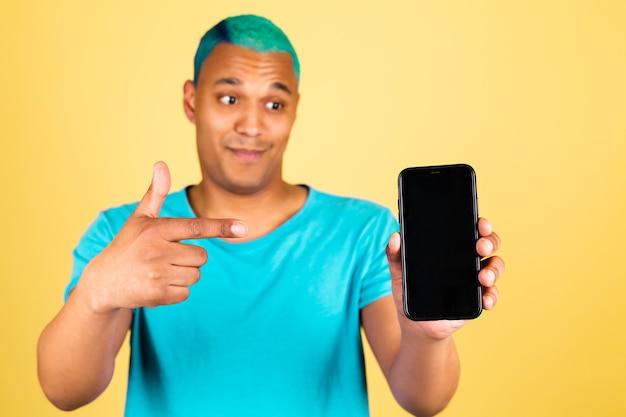 검은 색 빈 화면에 휴대 전화 긍정적 인 행복 포인트 검지 손가락으로 노란색 벽에 캐주얼 흑인 아프리카 남자