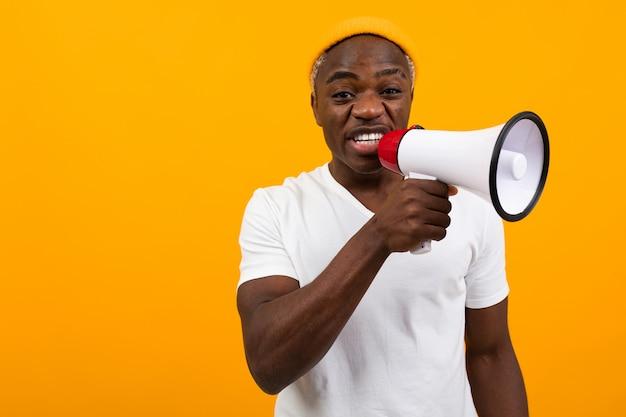 Черный африканец кричит в мегафон на желтом