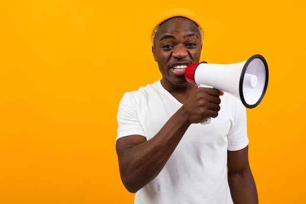 Black african man shouts in a megaphone on yellow