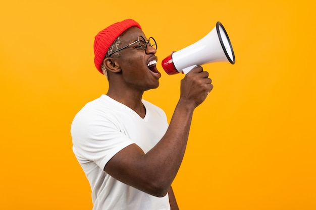 Black african man speaks in megaphone on isolated yellow